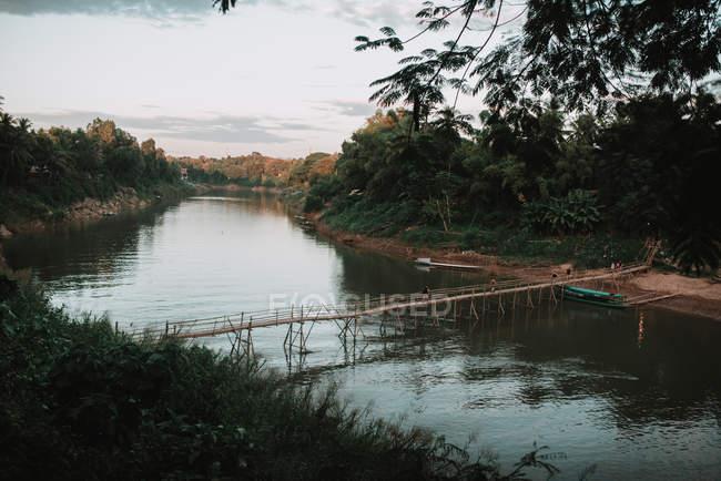 Vue sur la rivière qui coule et petit pont grogneux . — Photo de stock