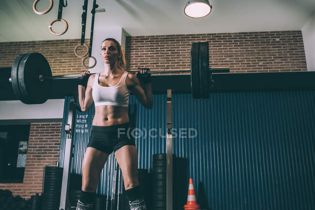 Fit blonde woman lifting bar weights while training in gym — Stock Photo
