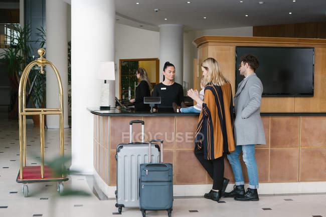 Giovane famiglia con bambino di registrazione presso la reception dell'hotel — Foto stock