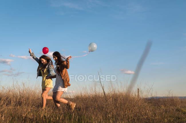 Hübsche junge Frauen Hand in Hand und mit Luftballons über Feld zusammen laufen — Stockfoto