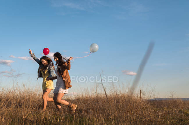 Pretty young women holding hands and running with balloons across field together. — Stock Photo