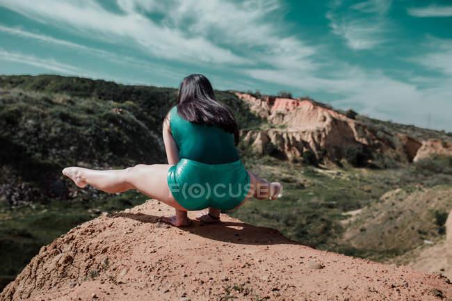Femme sportive debout sur les jambes et en étirant les jambes sur la colline — Photo de stock