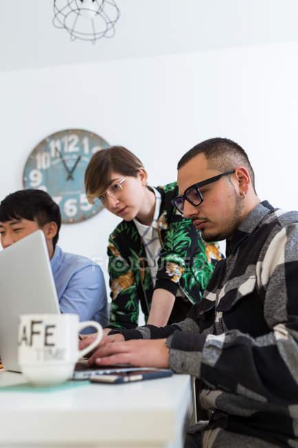 Gruppe von Kollegen, die Lösung von Aufgaben am Tisch zusammen — Stockfoto