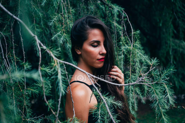 Pretty brunette woman posing in fir branches with eyes closed — Stock Photo