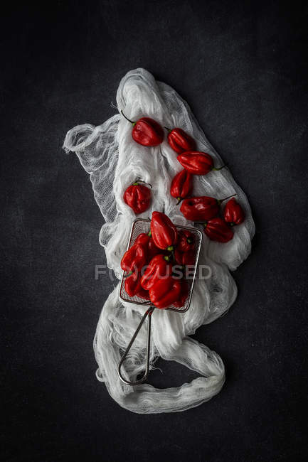 Still life fresh red peppers in sieve on fabric — Stock Photo