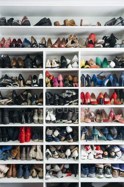Rack with different shelves filled with assortment of shoes. — Stock Photo