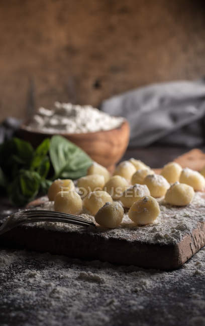 Rural still life of raw gnocchi on cutting board — Stock Photo