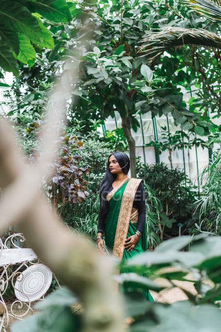 Ethnic young woman in traditional clothes standing at garden. — Stock Photo