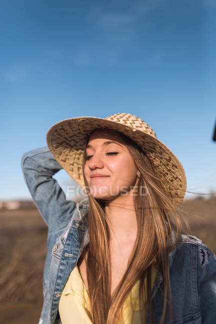 Pretty woman holding hat and enjoying nature with eyes closed. — Stock Photo