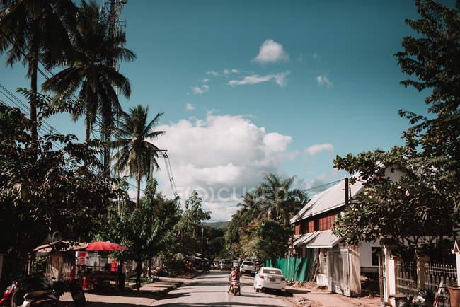 Rückansicht der Person, die fährt Roller durch tropische Dorf im sonnigen Tag — Stockfoto