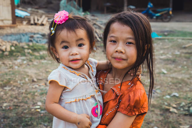 LAOS- FEBRUARY 18, 2018: Cheerful young sisters standing in village and looking at camera. — Stock Photo
