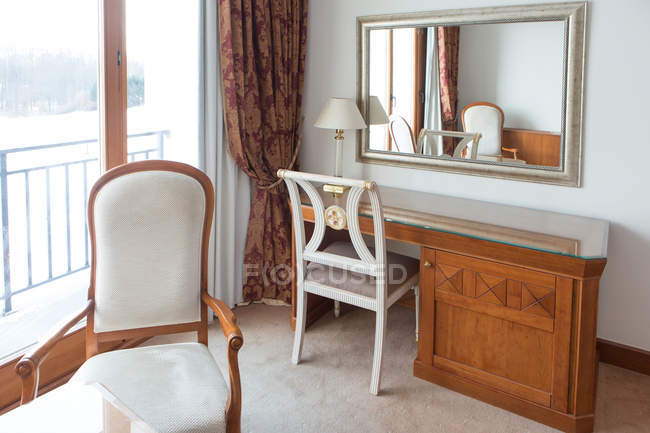 Wooden table with chair and mirror in hotel room. — Photo de stock