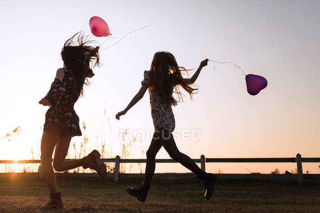 Silhouettes of girls running with heart-shaped balloons in nature. — Stock Photo