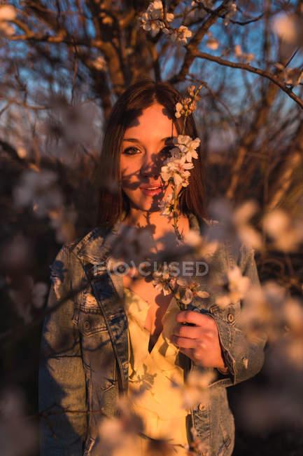 Чувственный женщина, стоя с цветами на ветке цветущее дерево — стоковое фото