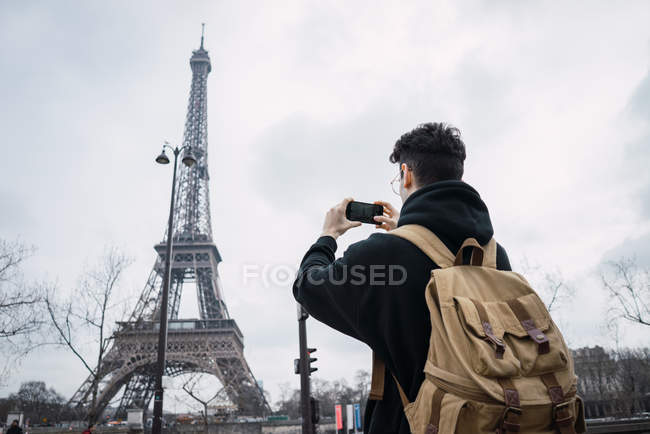 Back view of young man standing with phone and taking shots of Eiffel tower. — Stock Photo