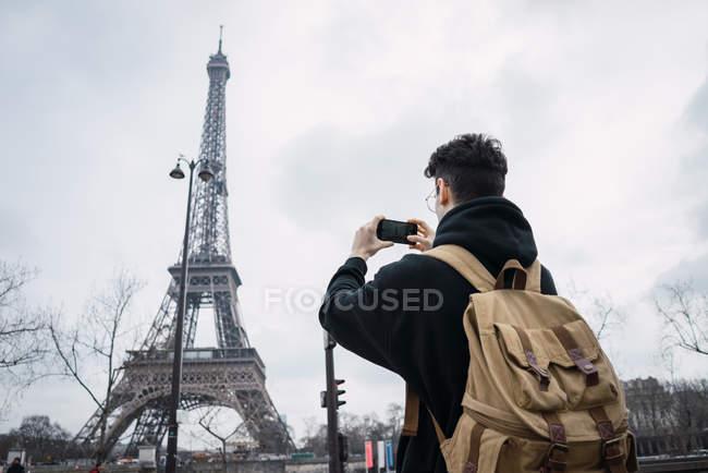 Резервного зору молодий чоловік стояв з телефону і приймають знімки Ейфелева вежа — стокове фото