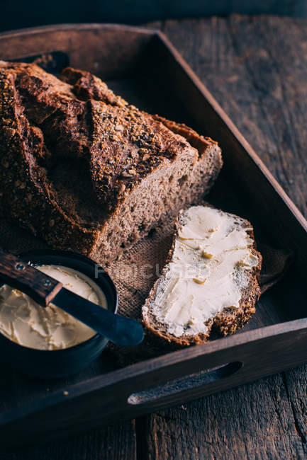 Rustic bread with butter on wooden tray — Stock Photo