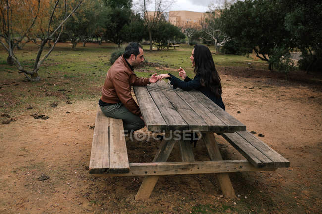 Mature couple sitting and holding hands at wooden table in park. — стоковое фото
