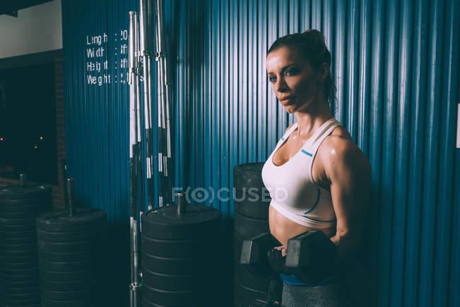 Femme blonde fit, soulever des poids pendant l'entraînement au gymnase — Photo de stock