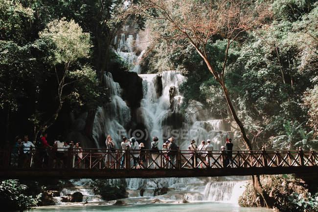 Лаос, Луанг Прабанг: Групи туристів, стоячи на мосту і, дивлячись на водоспад в тропічному лісі. — стокове фото