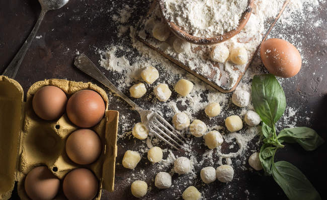 Directly above view of table with raw gnocchi and ingredients — Stock Photo