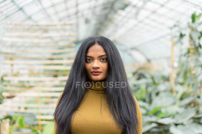 Young stylish Indian woman with backpack standing in hothouse. — Stock Photo