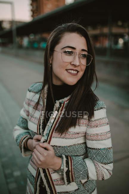 Jeune femme élégante décontractée permanent sur la rue et en regardant loin — Photo de stock
