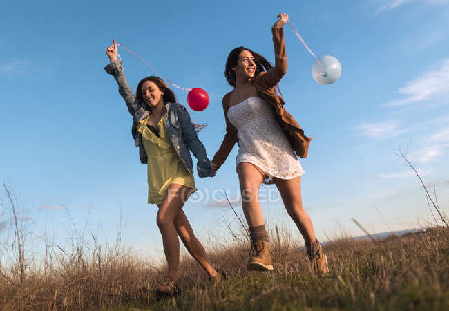 Young women holding hands and running with balloons at nature together. — Stock Photo