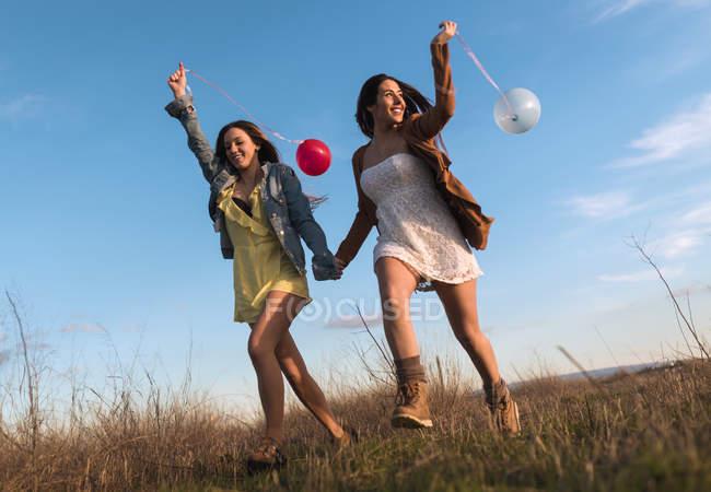 Молодих жінок взявшись за руки і працює з повітряних куль на природі разом — стокове фото