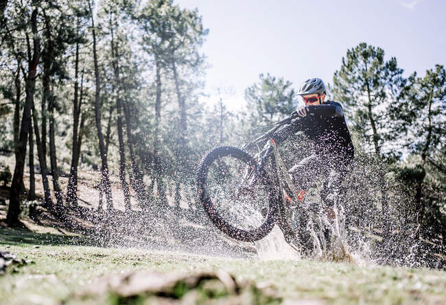 Ciclista de homem espirra paddle com bicicleta de montanha. — Fotografia de Stock