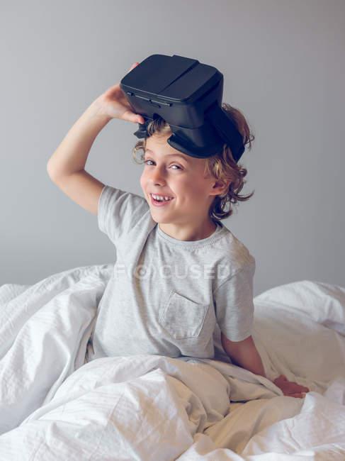 Улыбающийся мальчик снимает очки и смотрит в камеру — стоковое фото