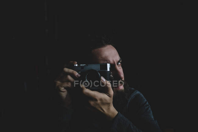 Photographer sitting over black and focusing with vintage camera — Stock Photo