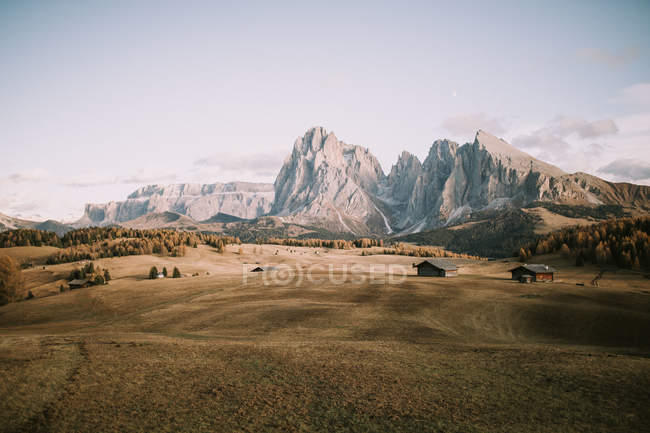Distant view to dry field with small houses on background of mountain peaks. — Foto stock