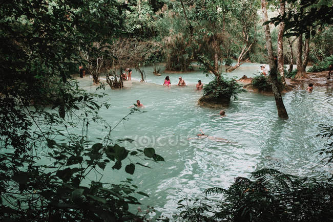 Лаос, Луанг Прабанг: Люди, купание в голубой воде лесного озера — стоковое фото