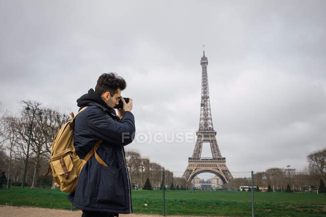 Side view of young man standing with camera and taking shots of Eiffel tower. — Stock Photo