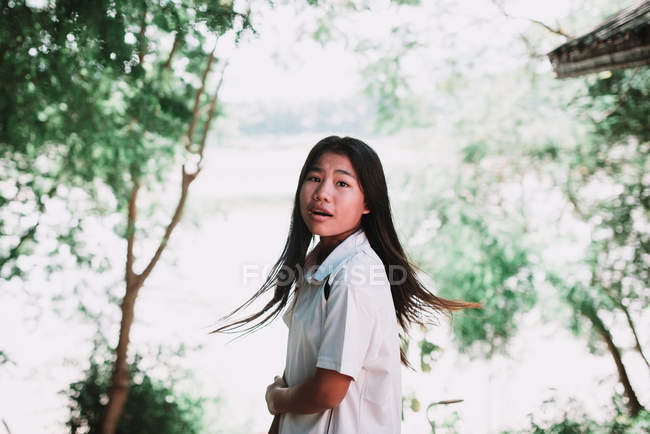 LAOS, LUANG PRABANG: Pretty local woman standing in green forest and looking over shoulder at camera. — Stock Photo