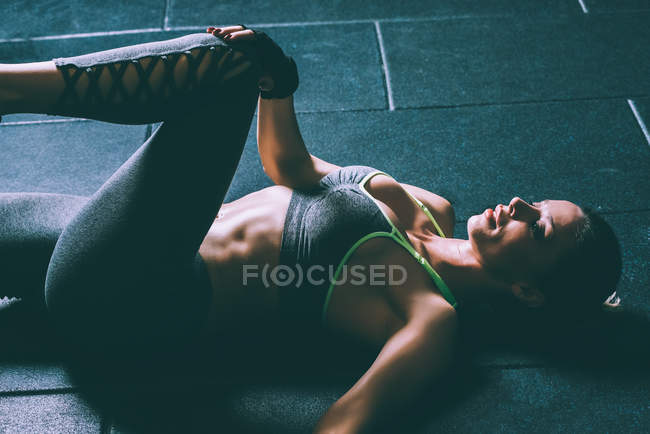 Fit blonde woman lying on floor and doing crunches in gym — Stock Photo