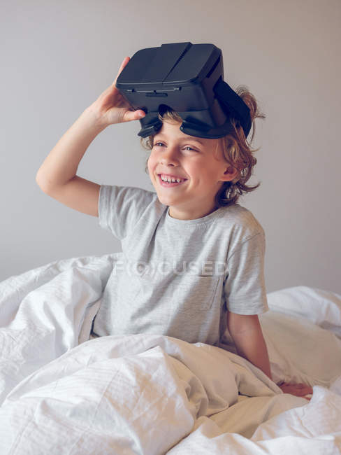 Cute boy lying on bed and taking off VR glasses — Stock Photo