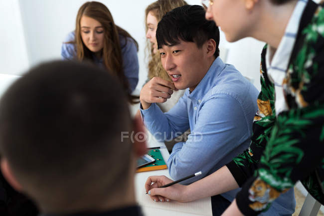 Group of multiracial coworkers talking to each other at table. — Stock Photo