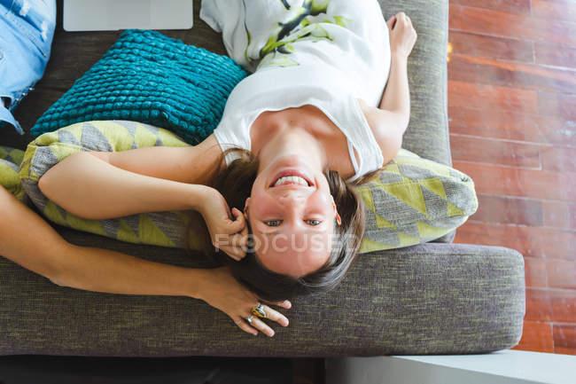 Прямо над вид веселий жінка, сидячи на дивані і дивитися на камеру — стокове фото