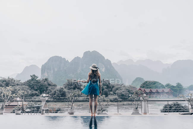 Back view of woman in dress standing on under rain and looking at tropical mountains. — Stock Photo