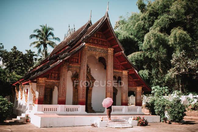 Visão traseira do turista irreconhecível andando sob guarda-chuva no templo — Fotografia de Stock