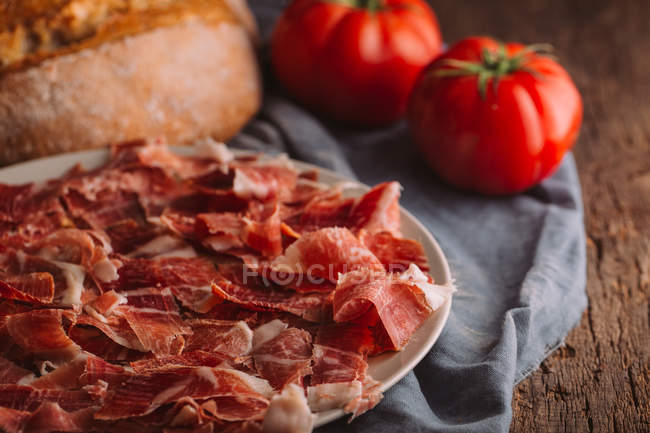 Still life of ham with tomatoes and bread — Stock Photo