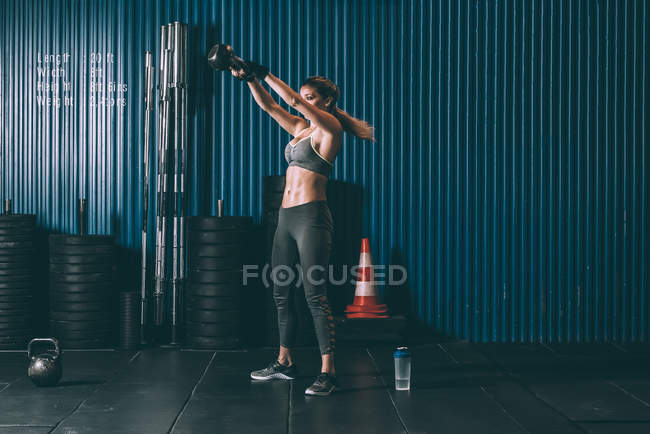 Fit woman training with kettlebell in gym — Stock Photo