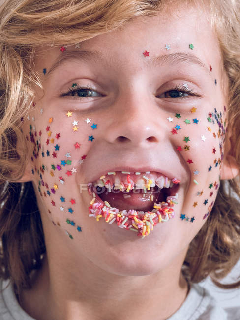 Portrait of cheerful boy with confetti on face — Stock Photo