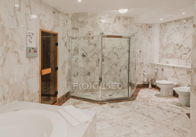 View to luxury bathroom interior with marble tiled walls — Stock Photo