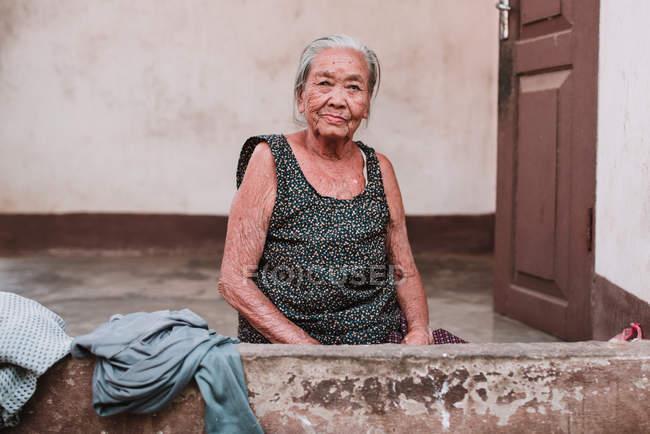 LAOS, LUANG PRABANG: Senior woman sitting at house door and looking at camera. — Stock Photo