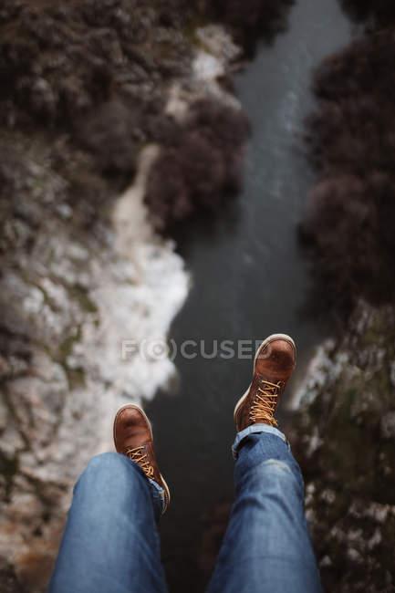 Guardando giù vista del turista che si siede sul bordo sopra il piccolo fiume — Foto stock