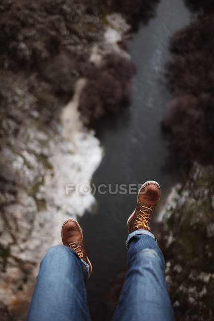Looking down view of tourist sitting on edge over small river. — Foto stock