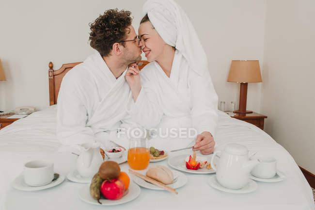 Pareja romántica desayunando en la cama del hotel - foto de stock